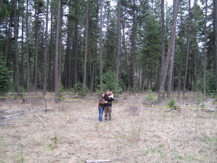 Lance and Lorinda standing on the future building site of the farmhouse in Idaho in the forest